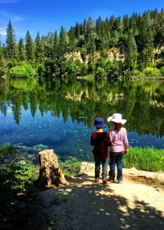 Boy and girl standing by a lake in a forest - friendship card - Photo by Donna Greene